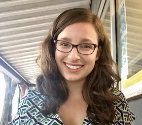 A portrait of Sarah Singer: a woman with long, curly brown hair and glasses