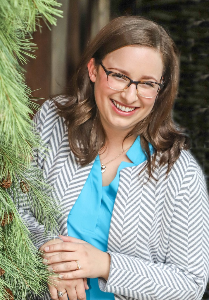 Sarah Singer, a white woman with brown hair and glasses. She is wearing a herringbone white and gray cardigan and blue shirt.
